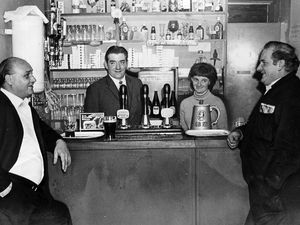 """nostalgia pic. Wolverhampton. Wolverhampton Transport Club, at Park Lane, Low Hill, Wolverhampton, in November 1969, which was for bus drivers, conductors and other transport staff. 'Known as 'the book ends, Terry Longsden and Nobby Clarke (right) stand in their regular spot at the bar of the Park Lane club, while club chairman Norman Robbins, and Margaret Kelly, wife of the steward, look on,"""" reads the caption pasted on the back of this print in the Express and Star picture library (in the basement archive at Queen Street, and copied in situ on Tuesday, May 18, 2021). The accompanying story says 'Wolverhampton's Transport Club, with a history dating back well over 30 years, and with a present day membership of about 1,000 (is) probably unique in the town in that it has two separate club rooms... at Ward Street, which is between Horseley Field and Walsall Street, and Park Lane, Low Hill... The club at Park Lane opened in 1958 is conveniently adjacent to the depot there... """" The print has a datestamp of November 21, 1969, and the Express and Star copyright stamp. The story reveals that Wolverhampton's Transport Club was once in the editorial department of the Express and Star offices in Queen Street... 'in the section on the second floor occupied by the paper's feature writers there was, not long ago, a well equipped club, with a well patronised bar, two billiard tables and various other popular amenities. Today... in their place reign typewriters and telephones. The fact that the club has disappeared does not mean it no longer exists. The club flourishes, not in one part of the town, but two...' Library code: Wolverhampton nostalgia 2021.."""