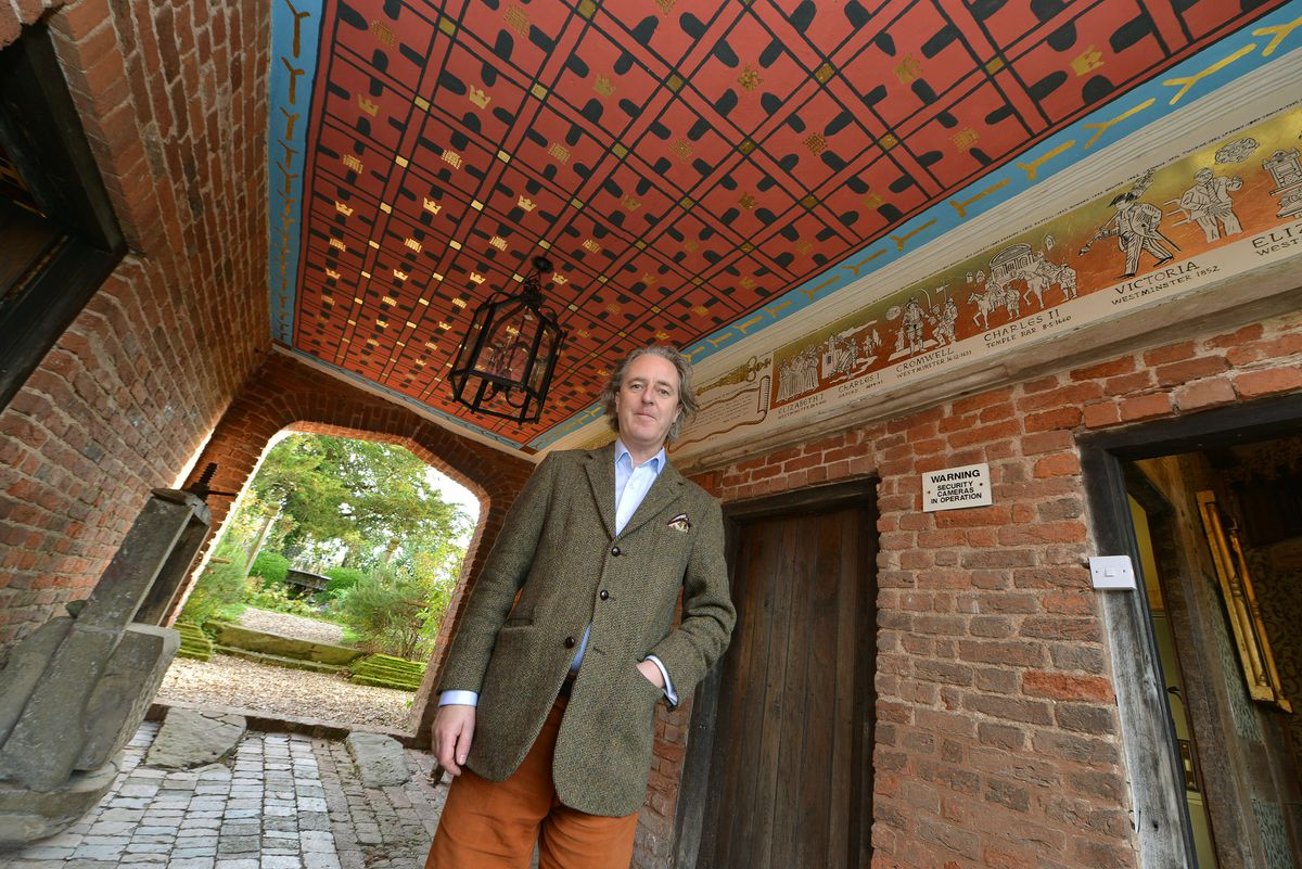 Artist Adam Dant with his 16-century style mural in the gatehouse at Upton Cressett Hall