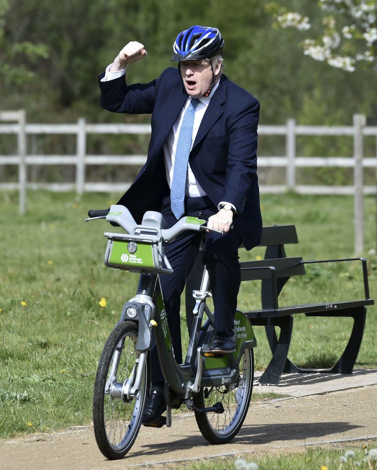 Prime Minister Boris Johnson rides a bike along the towpath in Stourbridge