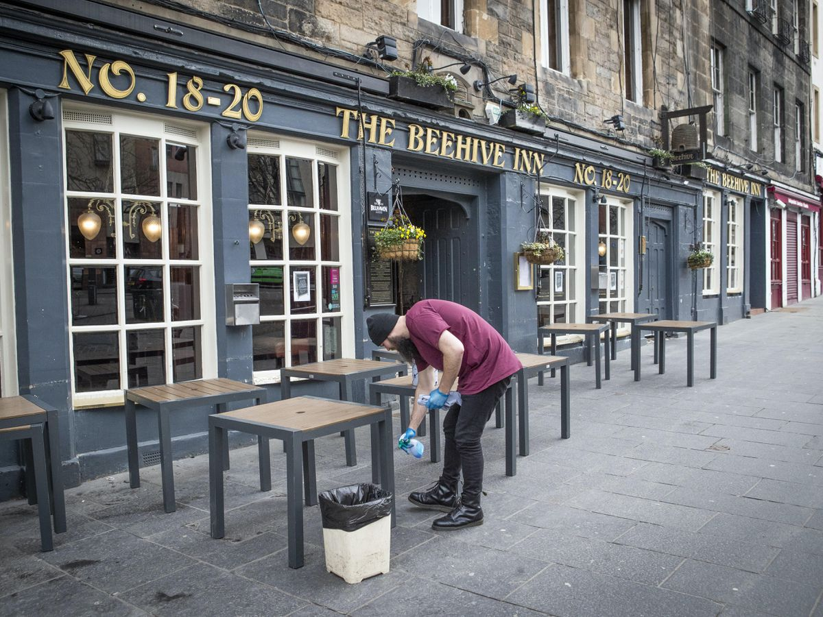 A worker cleans tables outside the Beehive Inn in Edinburgh