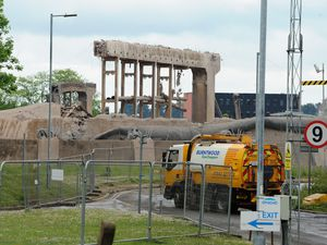 A road sweeper goes past what remains of one of the cooling towers