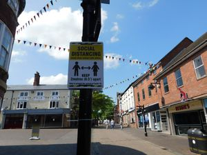 A sign reminding visitors to practice social distancing In Stone High Street