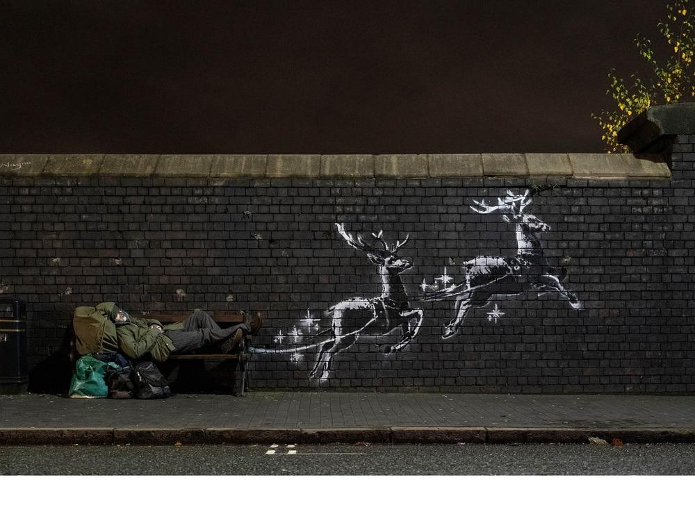 Reindeer pull homeless guy on workbench