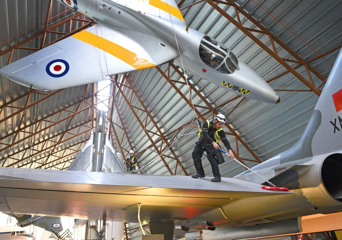 Members of Arco Professional Safety Services start the annual cleaning of the aircraft at RAF Cosford Museum, suspended on ropes