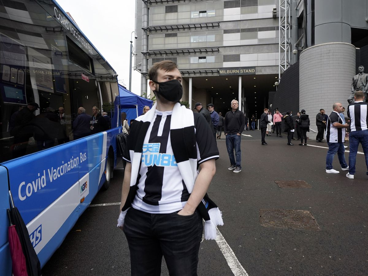 A Newcastle United fan waits for a Covid-19 vaccination at a vaccination bus outside the St James' Park stadium (Owen Humphreys/PA)