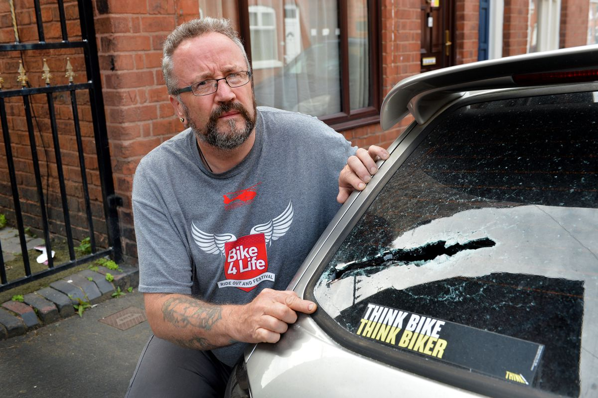 Mr Squires with more machete damage to the back of one of the cars