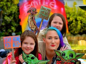 Laura McClure and daughters Elana and Willow with the colourful signs.