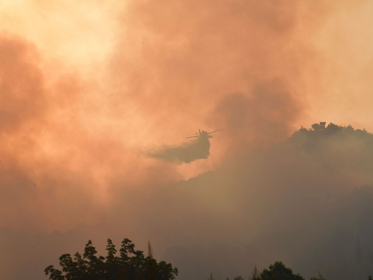 An aircraft drops water during a wildfire in ancient Olympia