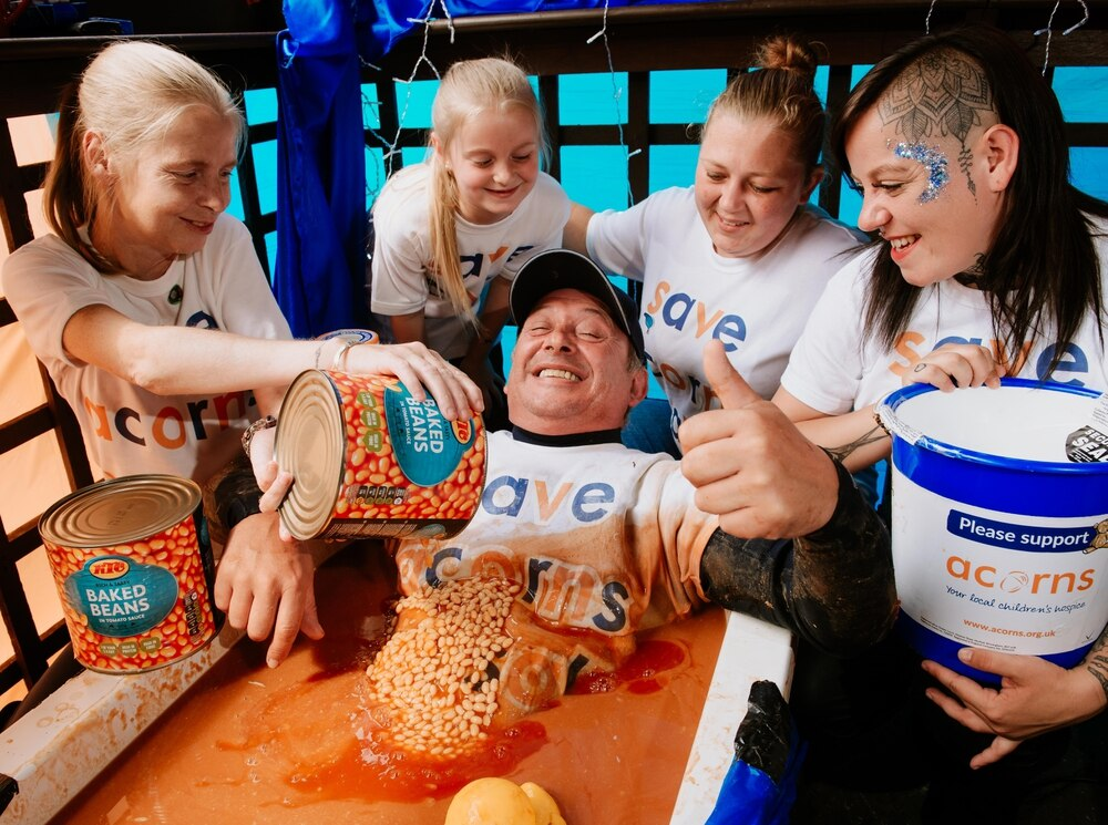 Acorns fundraiser bathes in baked beans in 24-hour charity bid