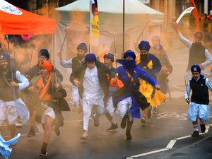 Members of Gatka teams run down Smethwick High Street with colourful flares