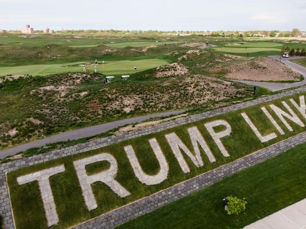 Patrons play golf near a giant branding sign at Trump Golf Links at Ferry Point in the Bronx