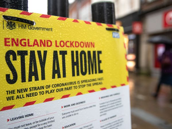 People walk past a Government sign warning people to stay at home on the High street in Winchester