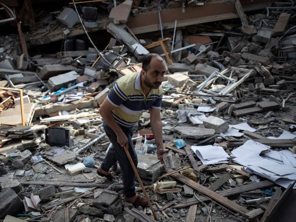 A Palestinian man inspects the damage of a house destroyed by an early morning Israeli airstrike, in Gaza City