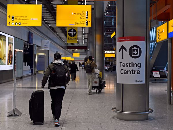 A passenger walks past a sign for the Covid testing centre in Heathrow's Terminal 5