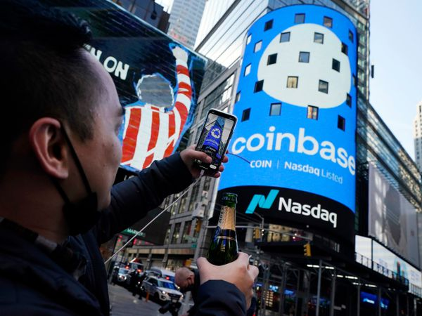 Coinbase employee Daniel Huynh holds a celebratory bottle of champagne as he photographs outside the Nasdaq MarketSite