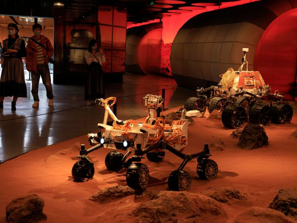 Visitors pass by an exhibition depicting rovers on Mars